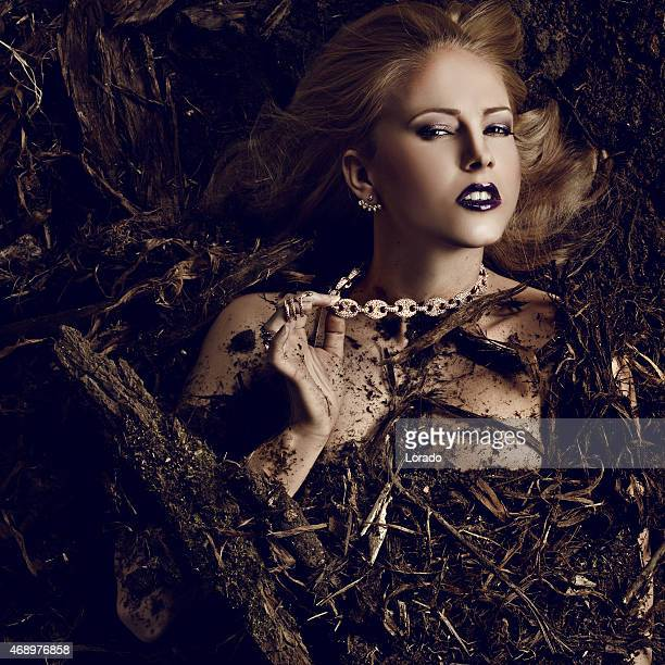 blond woman wearing luxury jewellery laying down in dirt - animal finger stock photos and pictures
