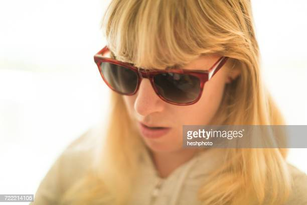blond woman wearing sunglasses looking down - heshphoto stockfoto's en -beelden