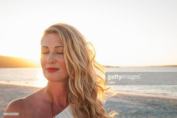 Blond woman with eyes closed on beach at dusk, Cape Town, South Africa