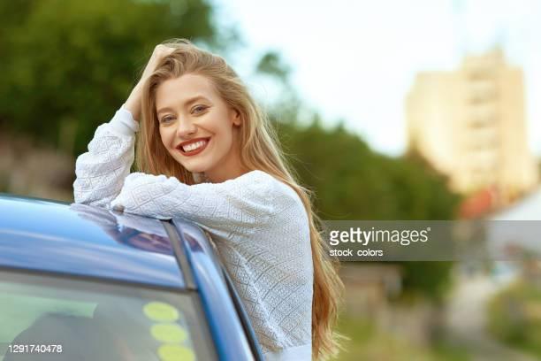 mulher loira com sorriso dentuço encostado no telhado do carro - olhos azuis - fotografias e filmes do acervo