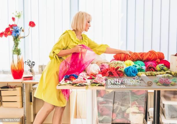 blond woman with yellow dress working in fashion atelier. - flerfärgad klänning bildbanksfoton och bilder