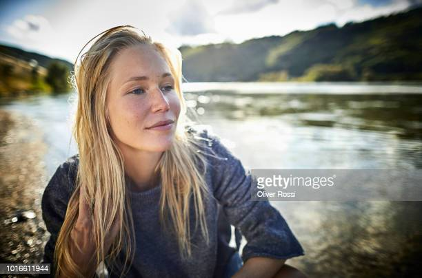 blond young woman at the riverbank - one young woman only stock pictures, royalty-free photos & images