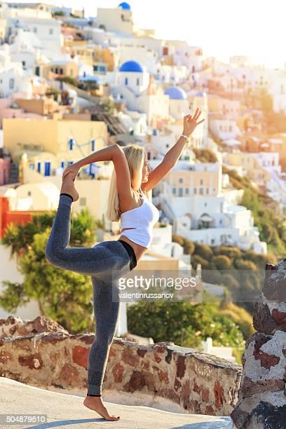 Blond jeune femme en équilibre au coucher du soleil à Santorin, Grèce