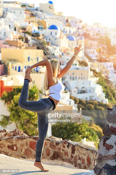 Blond young woman balancing at sunset in Santorini Greece
