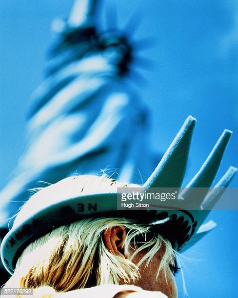 a blond young woman beeing disguised as the statue of liberty, new york - hugh sitton stock-fotos und bilder