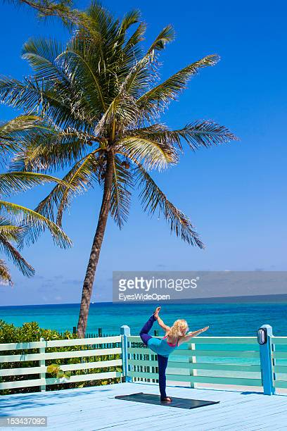 A blond young woman is practicing yoga asanas advanced postures gymnastics at the beach of Paradise Island with palmtrees and turquois blue water on...