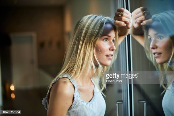 blond young woman looking out of window - desire stock pictures, royalty-free photos & images