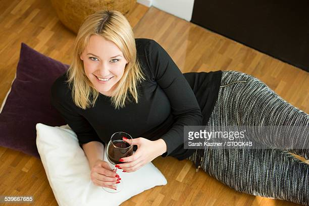 Blond young woman lying on floor with glass of red wine