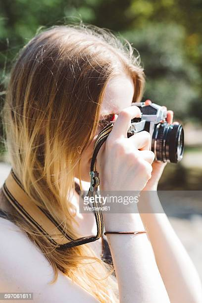 Blond young woman photographing outdoors