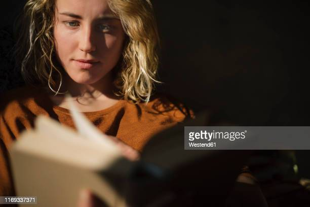 blond young woman reading a book - high contrast stock pictures, royalty-free photos & images