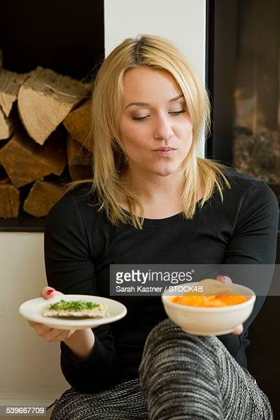Blond young woman sitting at the fireplace with chips and crispbread in her hand