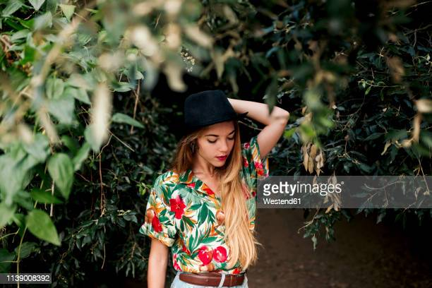 blond young woman surrounded by leaves and nature - umgeben stock-fotos und bilder