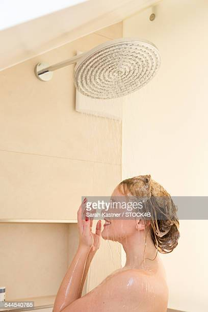 Blond young woman taking a shower