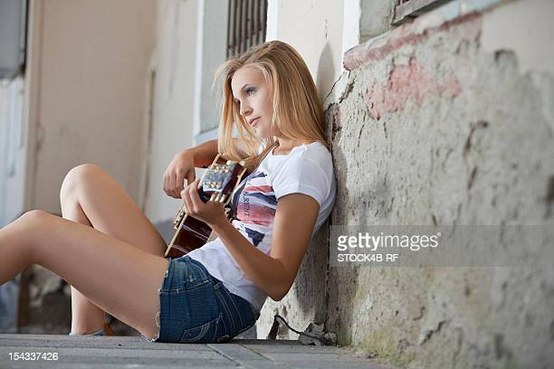 Blond young woman with electric guitar leaning against wall