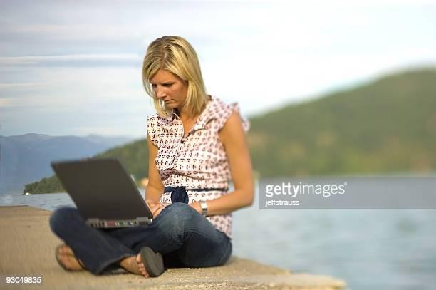 Blonde am See mit laptop