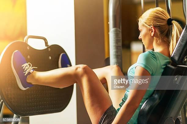 Rubia atleta haciendo se pone en cuclillas en gimnasio para nalga y piernas