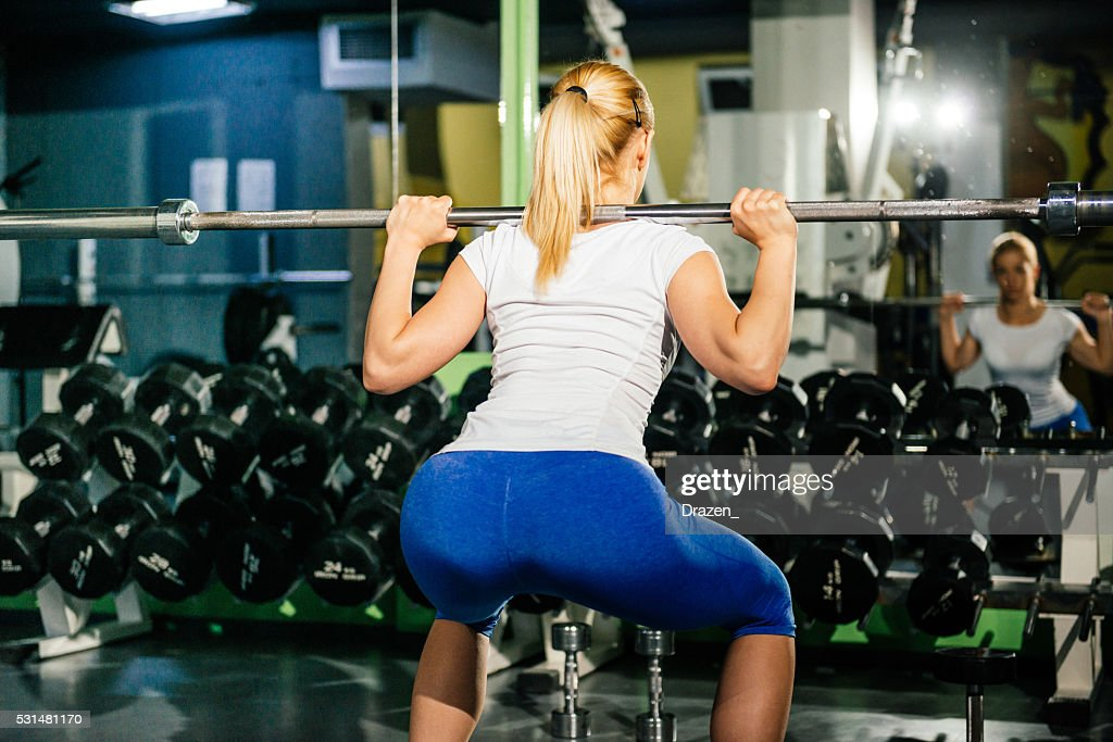 Blonde athlete doing squats in gym for buttocks and legs : Stock Photo