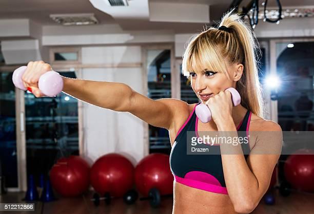 Rubia atleta hacer ejercicios con pesas en el gimnasio de boxeo formación