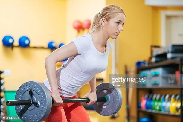 Rubia atleta hacer ejercicios con pesas en el gimnasio en cruz formación