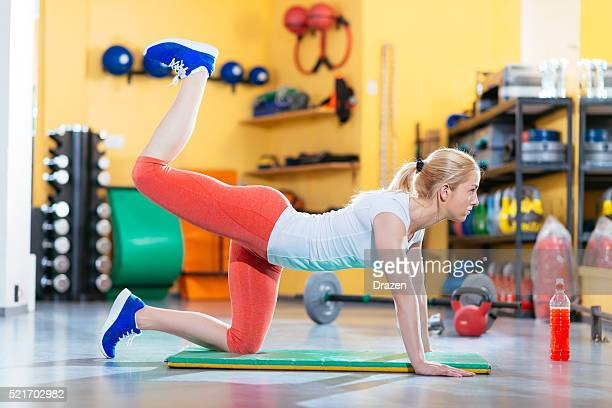 blonde athlete lifting legs for lower back and legs - lower back stock pictures, royalty-free photos & images