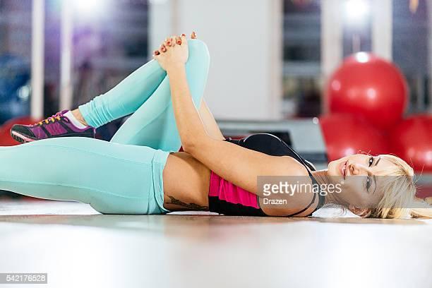 Rubia atleta de estiramiento después de entrenamiento en gimnasio y relaja