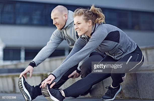 blonde athletic woman and coach stretching before training in city