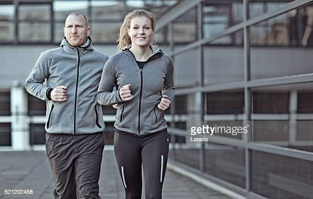 blonde athletic woman and shaved coach jogging together in city