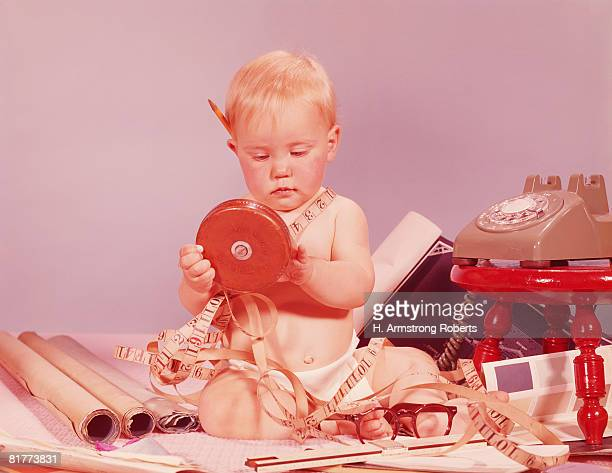 Blonde baby boy sitting with home improvement items. (Photo by H. Armstrong Roberts/Retrofile/Getty Images)