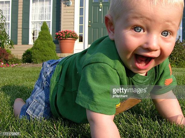 Blonde baby smiling and walking on grass