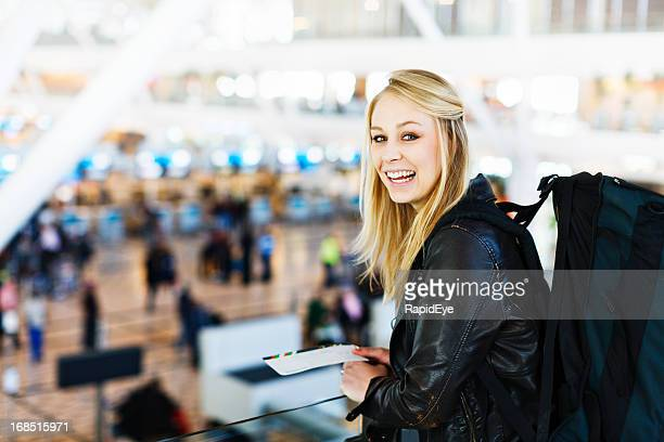 Blonde backpacker with boarding pass smiles excitedly at airport check-in