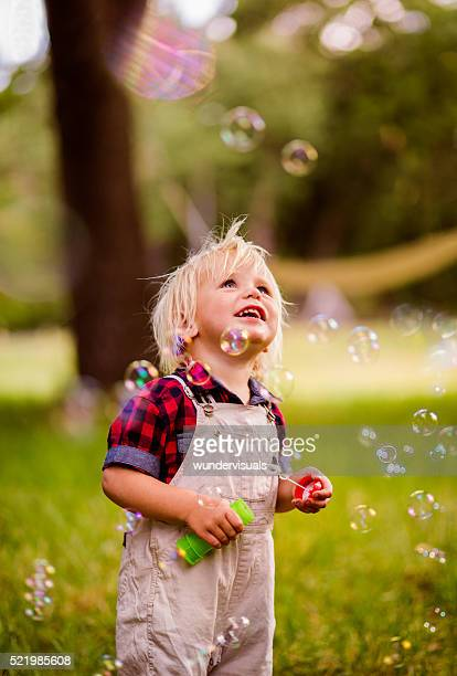 Blonde boy getting excited with soap bubbles at the park