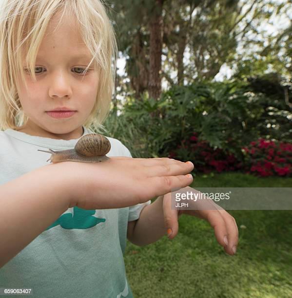Blonde boy holding snail