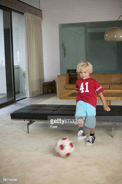 Blonde boy playing football in living room