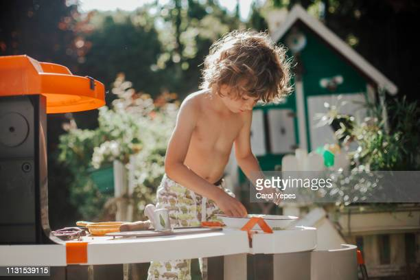 blonde boy playing to cook with cooking toys  in back yard - carol cook stock pictures, royalty-free photos & images