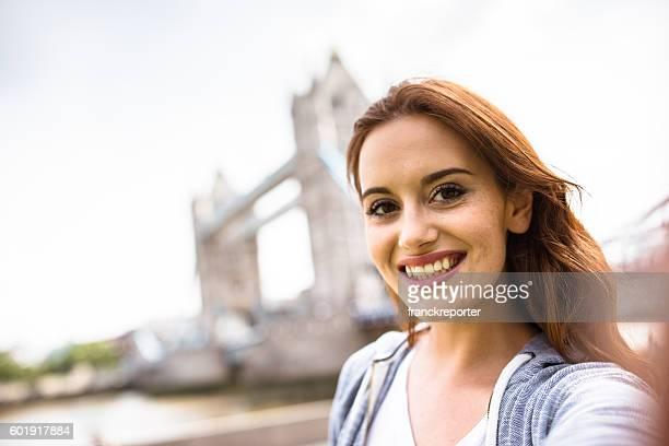 blonde british tourist doing a selfie on tower bridge