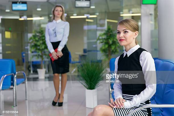 Blonde businesslike woman waiting in client service area