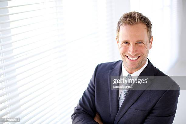 Blonde businessman smiling for cameraman
