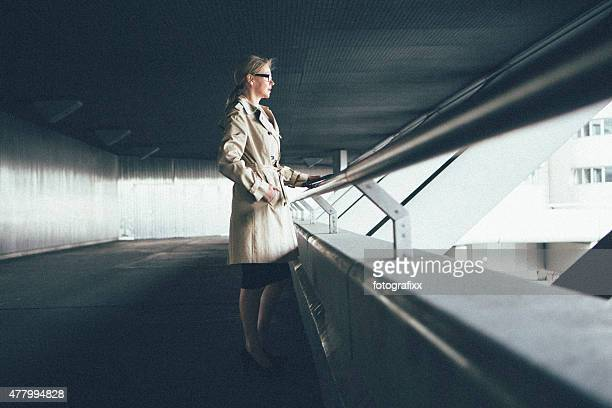 blonde businesswoman leans at railing looking away