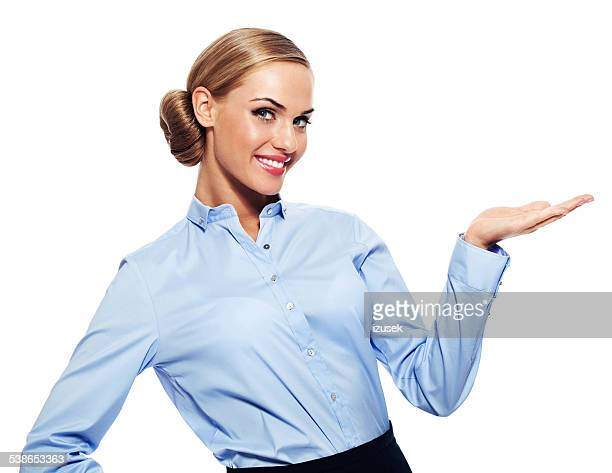 Blonde businesswoman pointing at copy space
