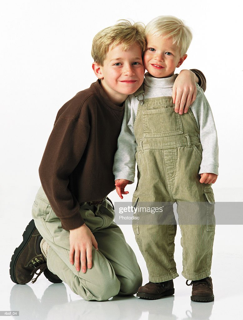 blonde caucasian boy in khakis on knees with arm around little brother in overalls : Foto de stock