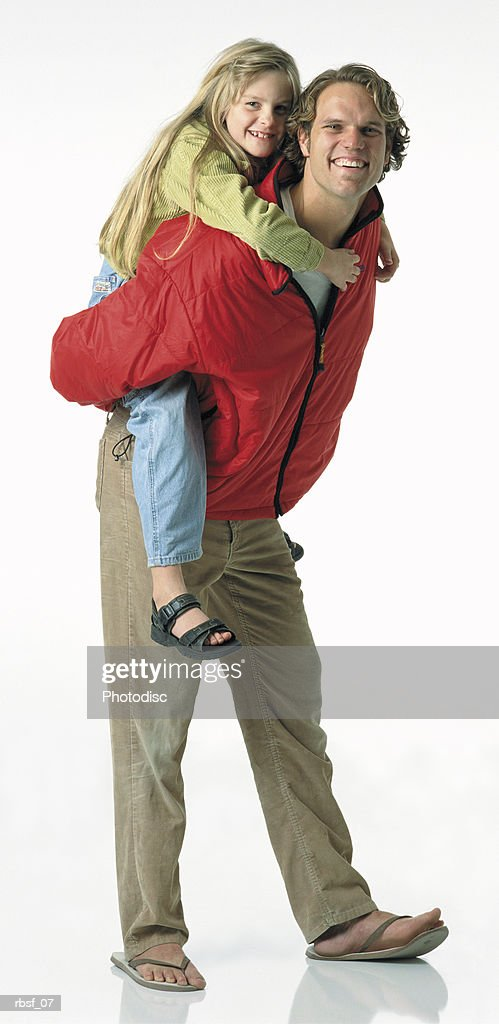 blonde caucasian dad in red jacket gives a blonde long haired daughter a piggy-back ride : Foto de stock