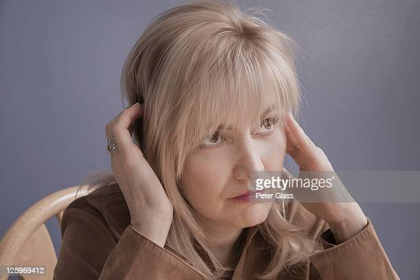 blonde caucasian female (52 years old) massaging temples - 50-59 years and women only fotografías e imágenes de stock