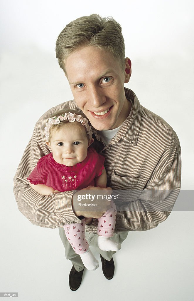 blonde caucasian single father stands with khaki shirt on while he holds baby in pink with a headband on : Foto de stock
