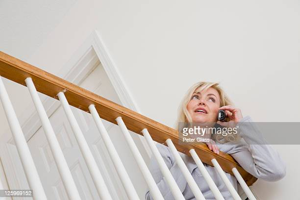 blonde caucasian woman, 51 years old, talking on her telephone while leaning over the balustrade - 50-59 years and women only fotografías e imágenes de stock