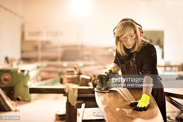 Blonde craftsperson power sanding wood