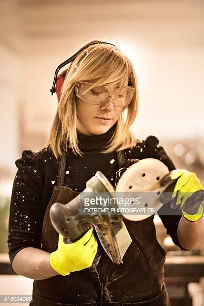 Blonde craftsperson with power sander