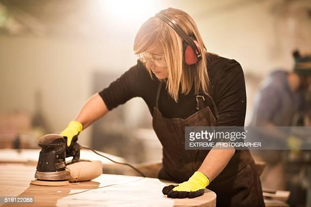 Blondine Kunsthandwerker arbeitet mit power-Bootsschuh Sander