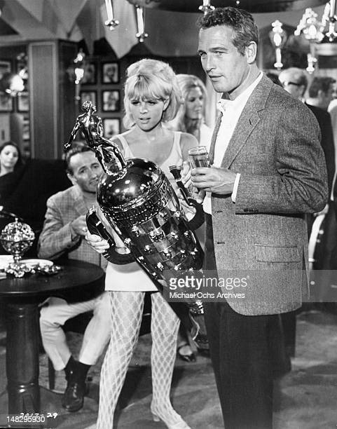 A blonde fan admires the Borg Warner Trophy won by Paul Newman in a race in a scene from the film 'Winning' 1969