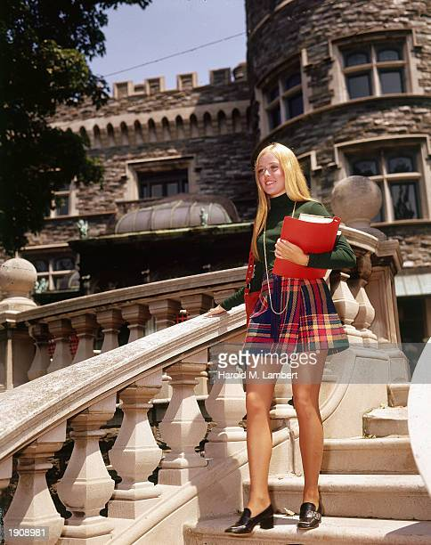 A blonde female college student wearing a plaid miniskirt walks down a flight of steps while holding her books early 1970s