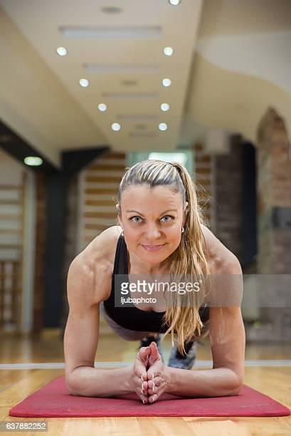 blonde femme faisant de planche statique de l'exercice dans la salle de sport  - blonde forte poitrine photos et images de collection